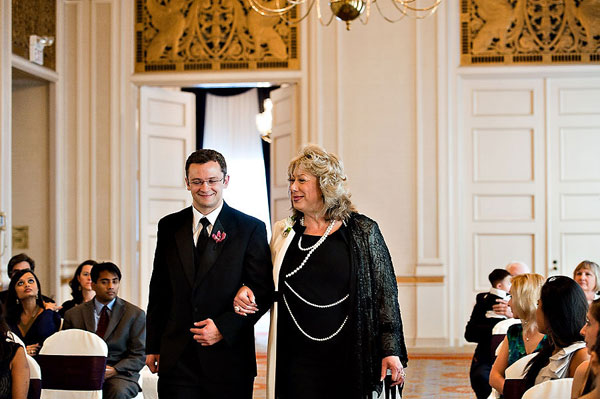 groomsman escorting mother of the bride to her seat