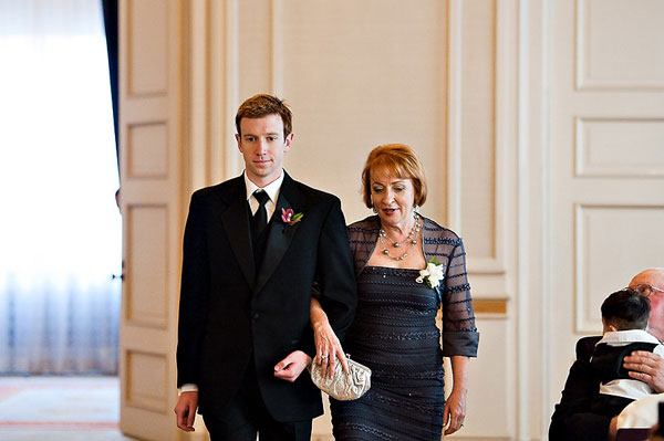 groomsman escorting mother of the groom to her seat