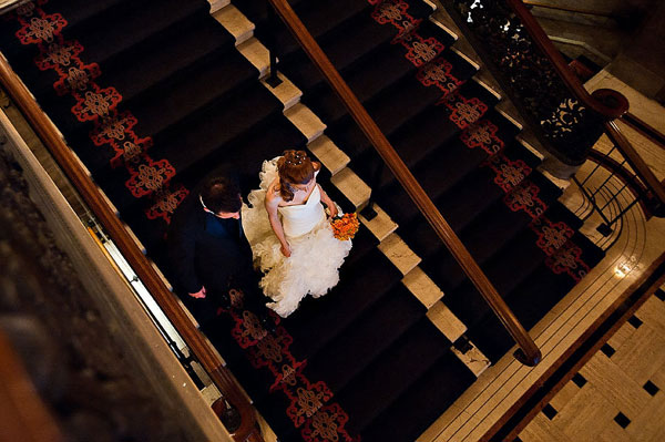 bride and groom walking down hotel stairs