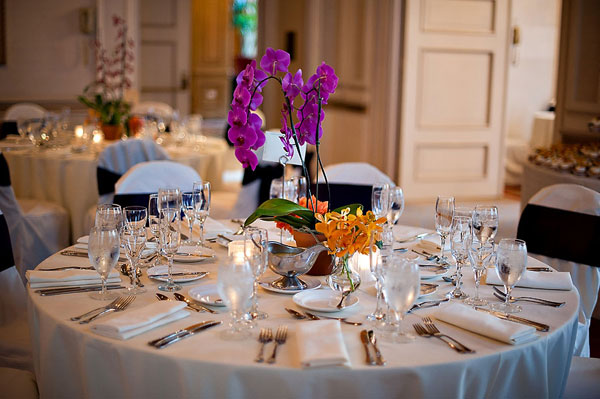 purple orchid and orange flower centerpieces