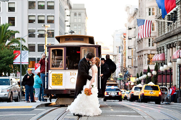 bride and groom kissing in front of streetcar trolley