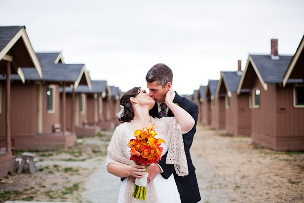 bride and groom kissing by row of cabins