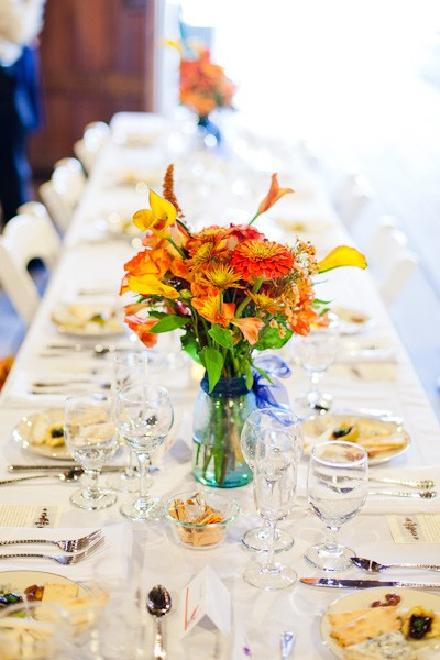 orange floral centerpiece in blue mason jar