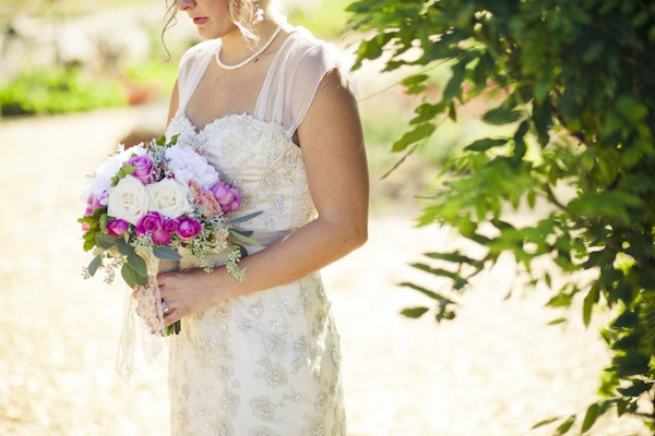 bride with white and purple rose bouquet