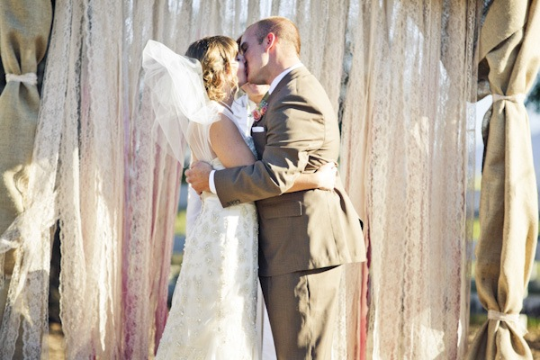 bride and groom kissing in front of lace ribbon ceremony backdrop