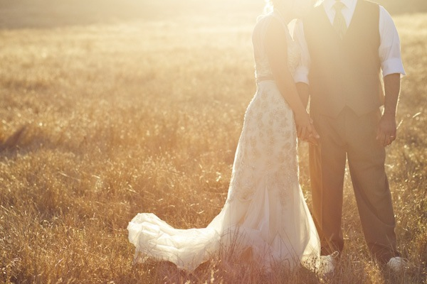 bride and groom holding hands at sunset