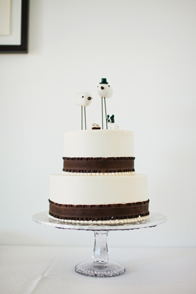 white wedding cake with chocolate ribbon and bird cake topper