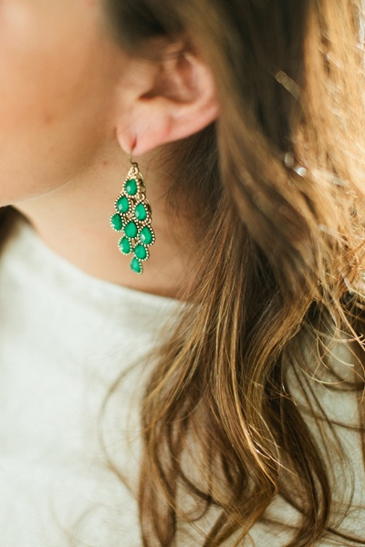 bride wearing green chandelier earrings