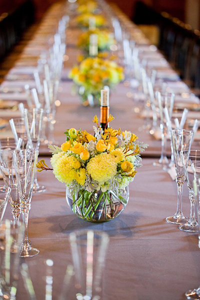 yellow centerpieces on long reception table