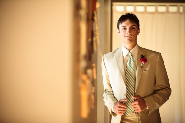 groom in beige suit and green striped tie