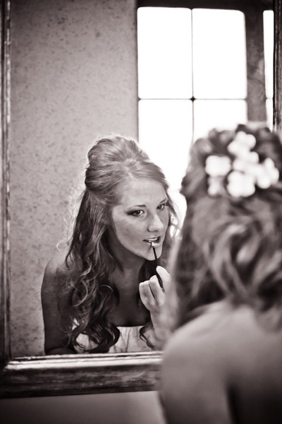 bride applying lip gloss
