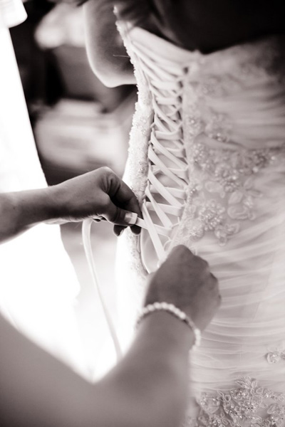 bride's dress being laced up