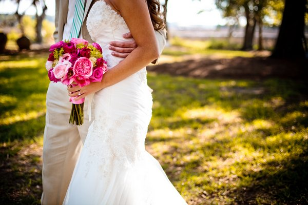 bride with pink rose bouquet walking with groom