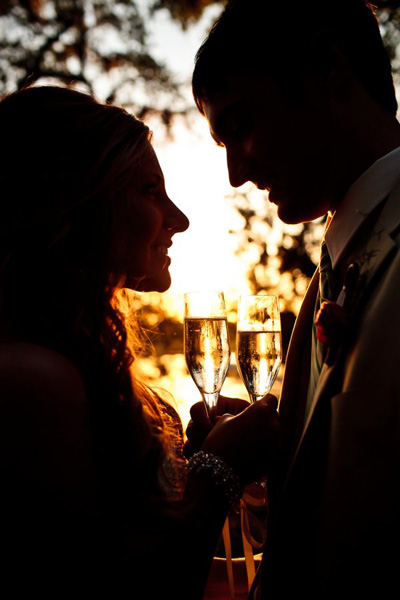 bride and groom with champagne at sunset