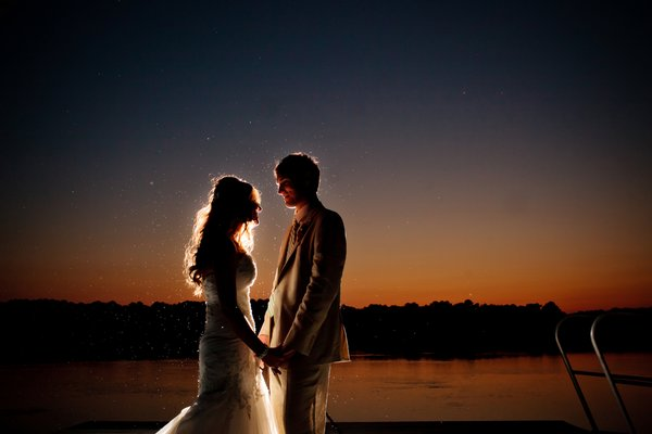 bride and groom by the river at night
