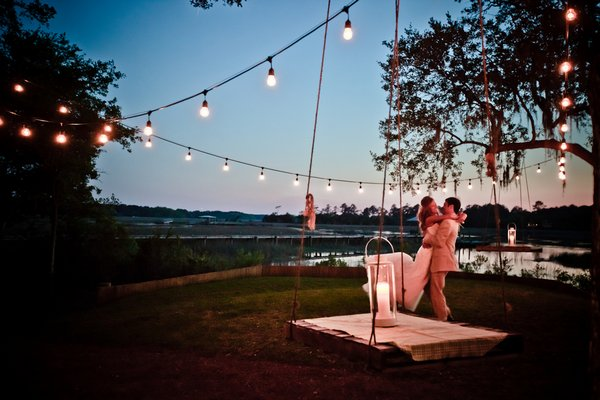 bride and groom hugging under string lights