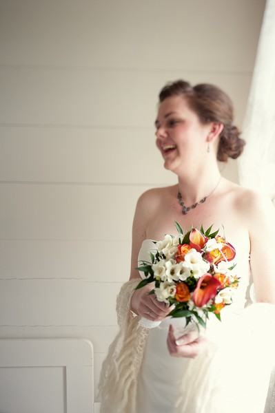 bride with orange and white bouquet