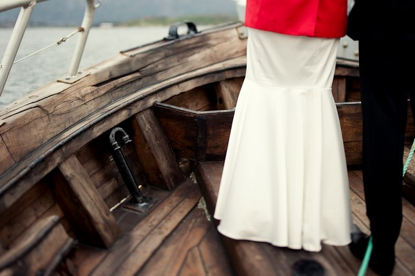 bride in red coat on boat