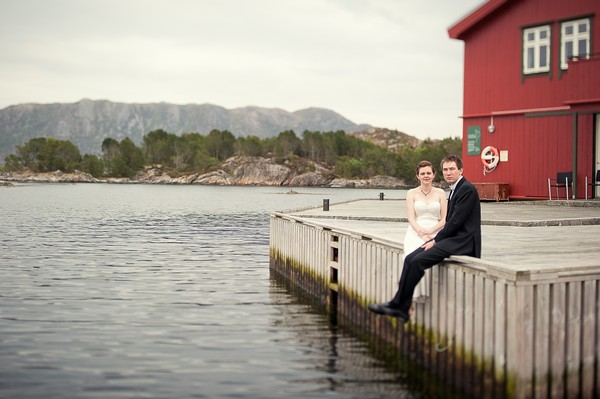 bride and groom sitting on the dock in Norway
