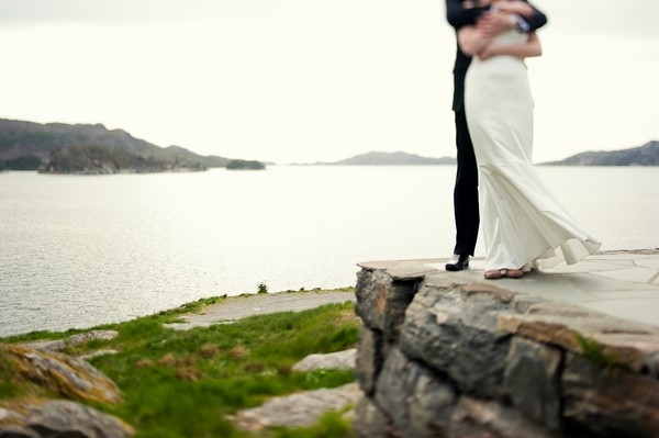bride and groom looking out at the sea in Norway