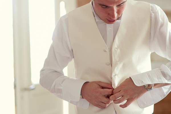 groom buttoning his vest