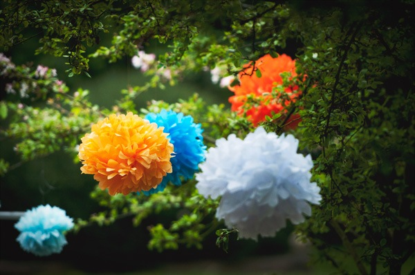 multi-colored tissue pom poms in garden wedding