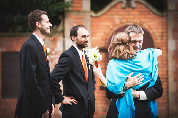 groom hugging bridesmaid