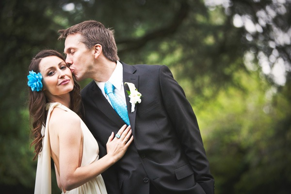 groom kissing bride on cheek