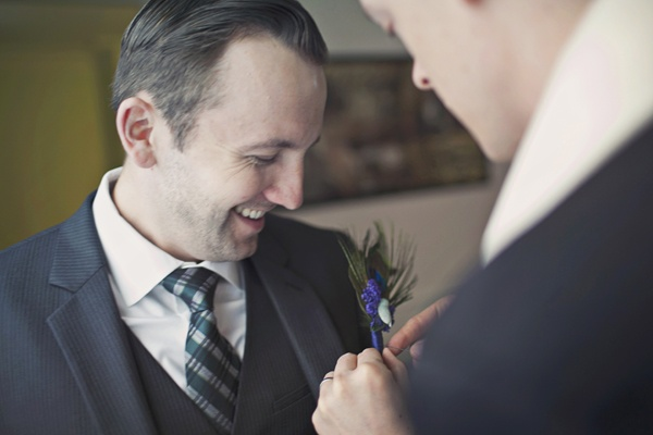 groomsman pinning boutonniere onto groom's jacket
