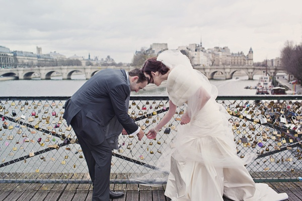 bride and groom adding lock to bridge in Paris