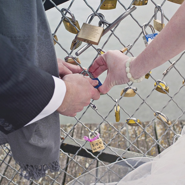 bride and groom adding lock to bridge