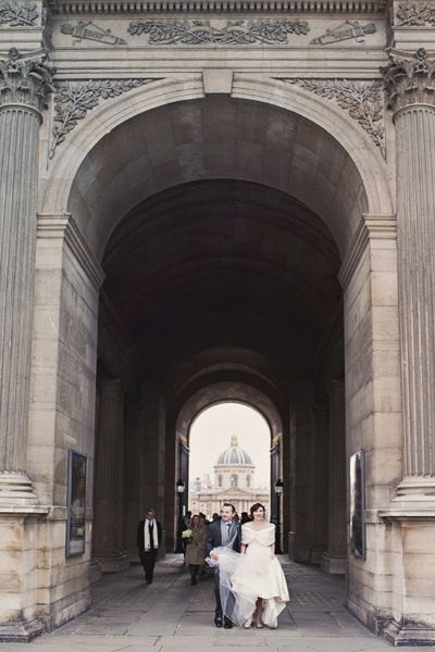 bride and groom walking though grand archway in Paris