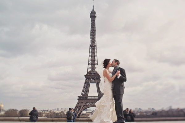 Bride and groom kissing by the Eiffel tower