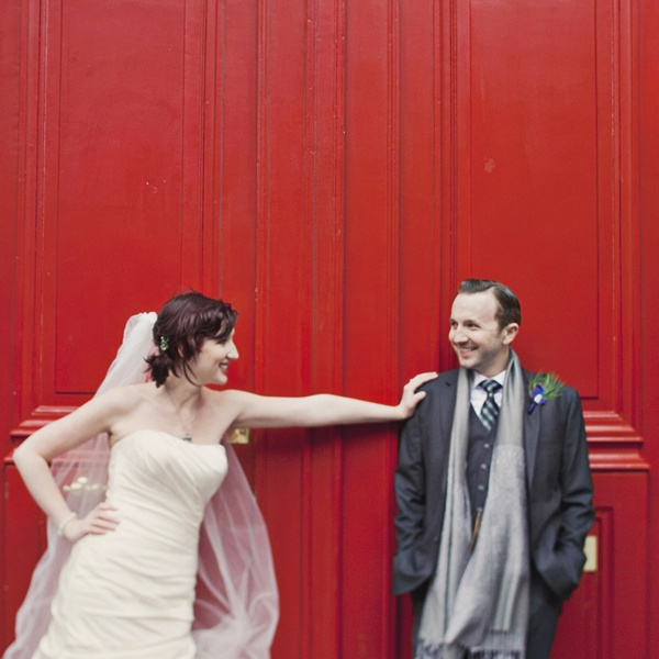 bride and groom in front of red french doors