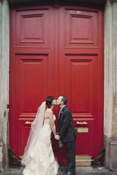 bride and groom kissing in front of red doors