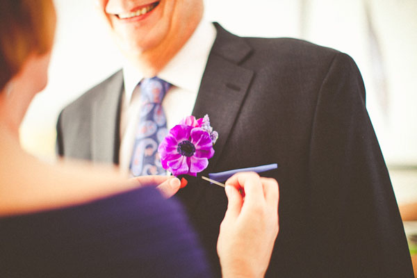 bride pinning purple anemone boutonniere on groom