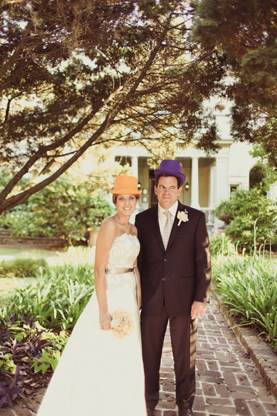 bride and groom in orange and purple top hats