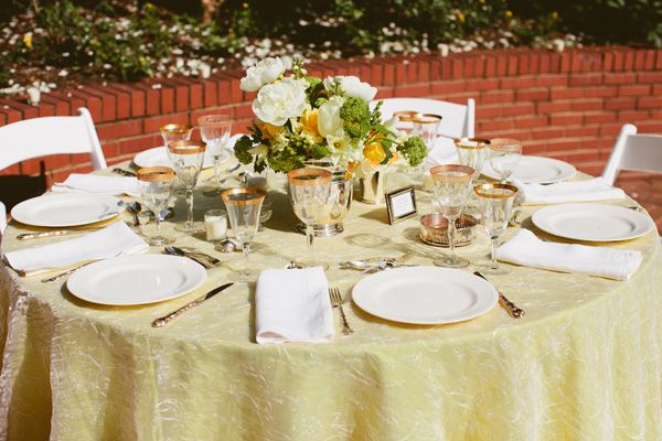 reception table with yellow tablecloth and white and yellow centerpiece