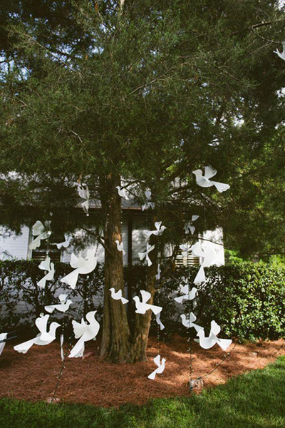 paper doves hanging in tree at wedding reception