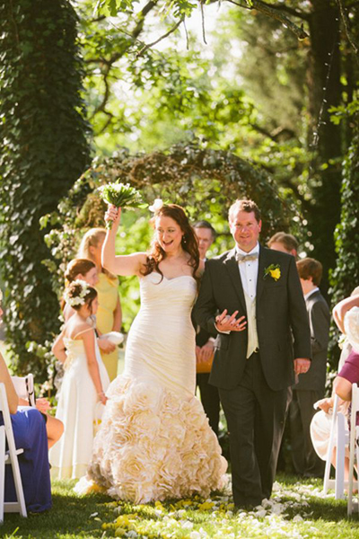 bride raising her bouquet as she walks down the aisle with her groom