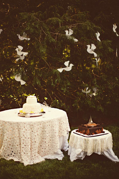 paper doves hanging in tree over wedding cakes