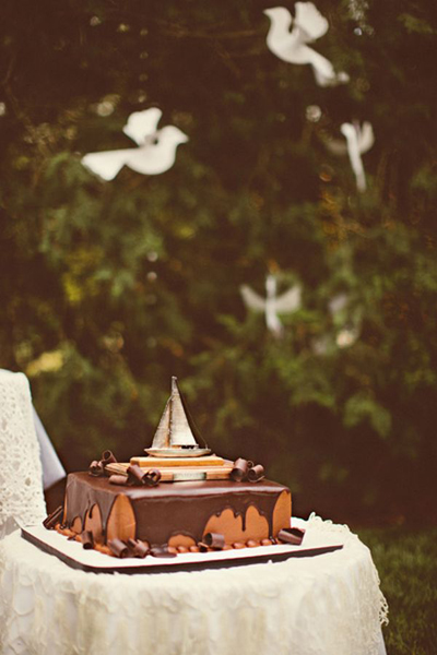 chocolate groom's cake with sailboat on top