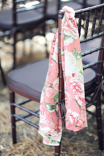 floral fabric tied to wedding chairs