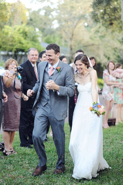 guests throwing birdseed at bride and groom