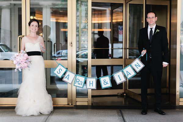 bride and groom with paper wedding banner