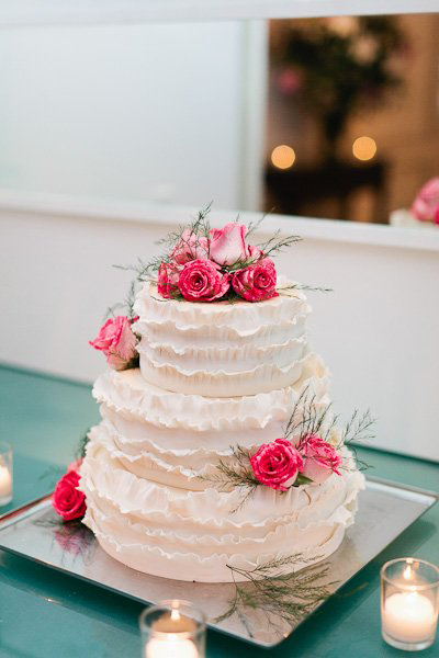 white ruffled wedding cake with pink roses
