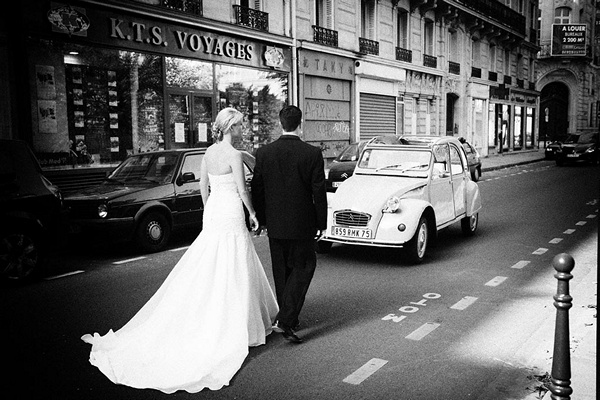 bride and groom walking down parisian street