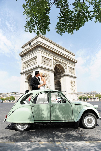 bride and groom in vintage car in front of l'arc de triomphe
