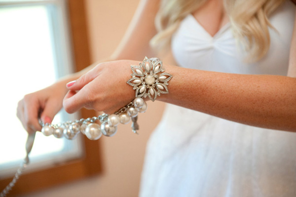 bride putting on pearl bracelet