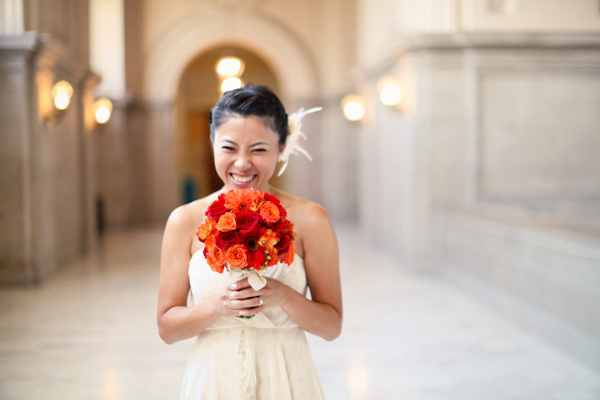 bride with orange and red bouquet
